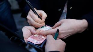 En camapgne électorale sur le marché de Concarneau (Bretagne), Marine Le Pen écrit sur un billet de 10 euros.