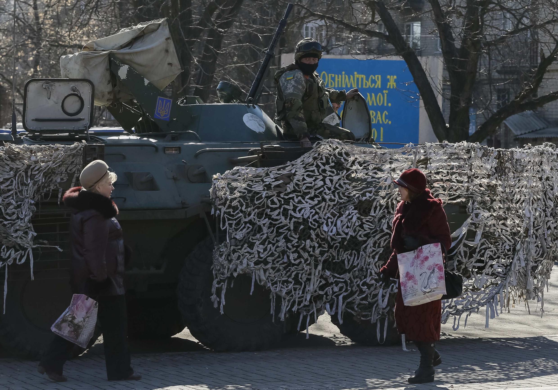 Habitantes de Artemivsk, no leste da Ucrânia, passam em frente a tanque do exército do país.