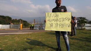 """Một người dân Venezuelan cầm tấm bảng ghi """"cần viện trợ nhân đạo ngay"""", ở phía trước trạm kiểm soát biên giới Tienditas, tại Cucuta, Colombia. Ảnh chụp ngày 06/02/2019"""