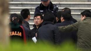 Công an mặc sắc phục và thường phục Trung Quốc bao vây một người tại địa điểm tập hợp của Hội thánh Tin Lành Thủ vọng tại Bắc Kinh ngày 10/4/11.