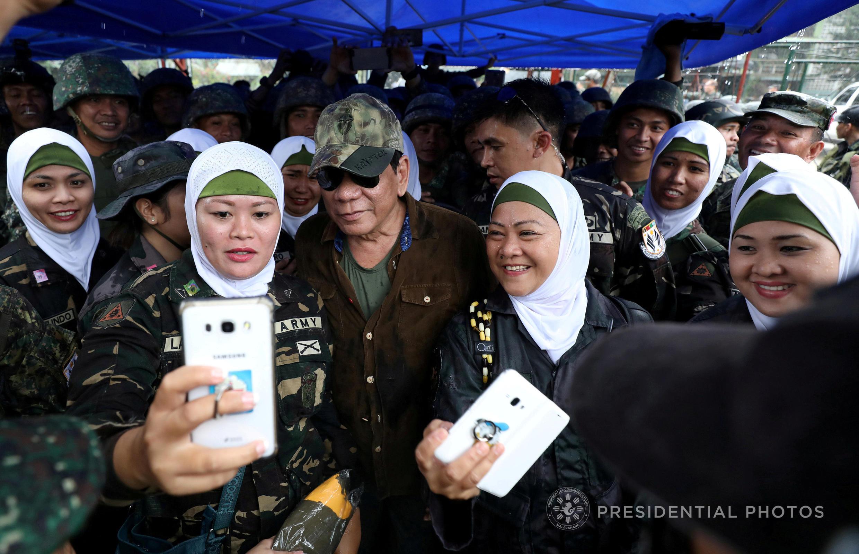Tổng thống Philippines Rodrigo Duterte (giữa) chụp ảnh với các quân nhân nữ khi tới thăm Bangolo, Marawi, ngày 17/10/2017.