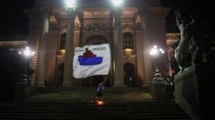 Des manifestants nationalistes intègrent désormais les cortèges. Ici un homme agite un drapeau avec la carte du Kosovo aux couleurs de la Serbie lors d'une manifestation à Belgrade, le 11 juillet 2020.