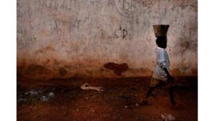 Une petite fille porte un seau d'eau sur sa tête.