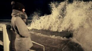 A woman faces the storm-hit sea at Lion-sur-Mer, north-west France