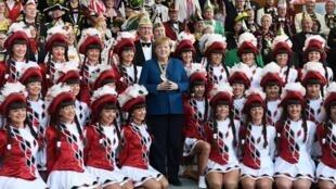 德国总理默克尔22日在总理府与一群来访的舞者留念。