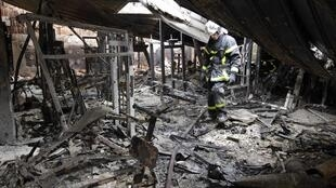 French firemen inspect the remnants of a torched school in Amiens following riots