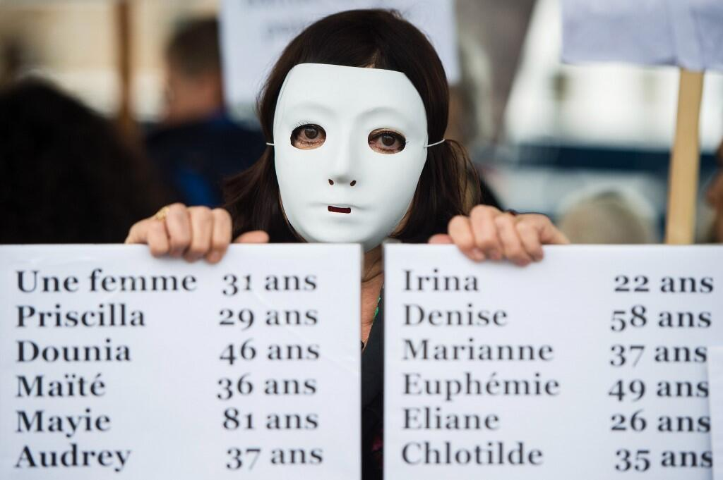 A woman holds a placard bearing the names of femicide victims in France in 2019.