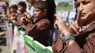 Palestinian children take part in a rally in front of the Red Cross headquarters in Gaza City marking Palestinian Prisoners Day