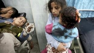 Crianças feridas depois de um ataque aéreo israelense recebem atendimento num hospital ao norte da Faixa de Gaza.