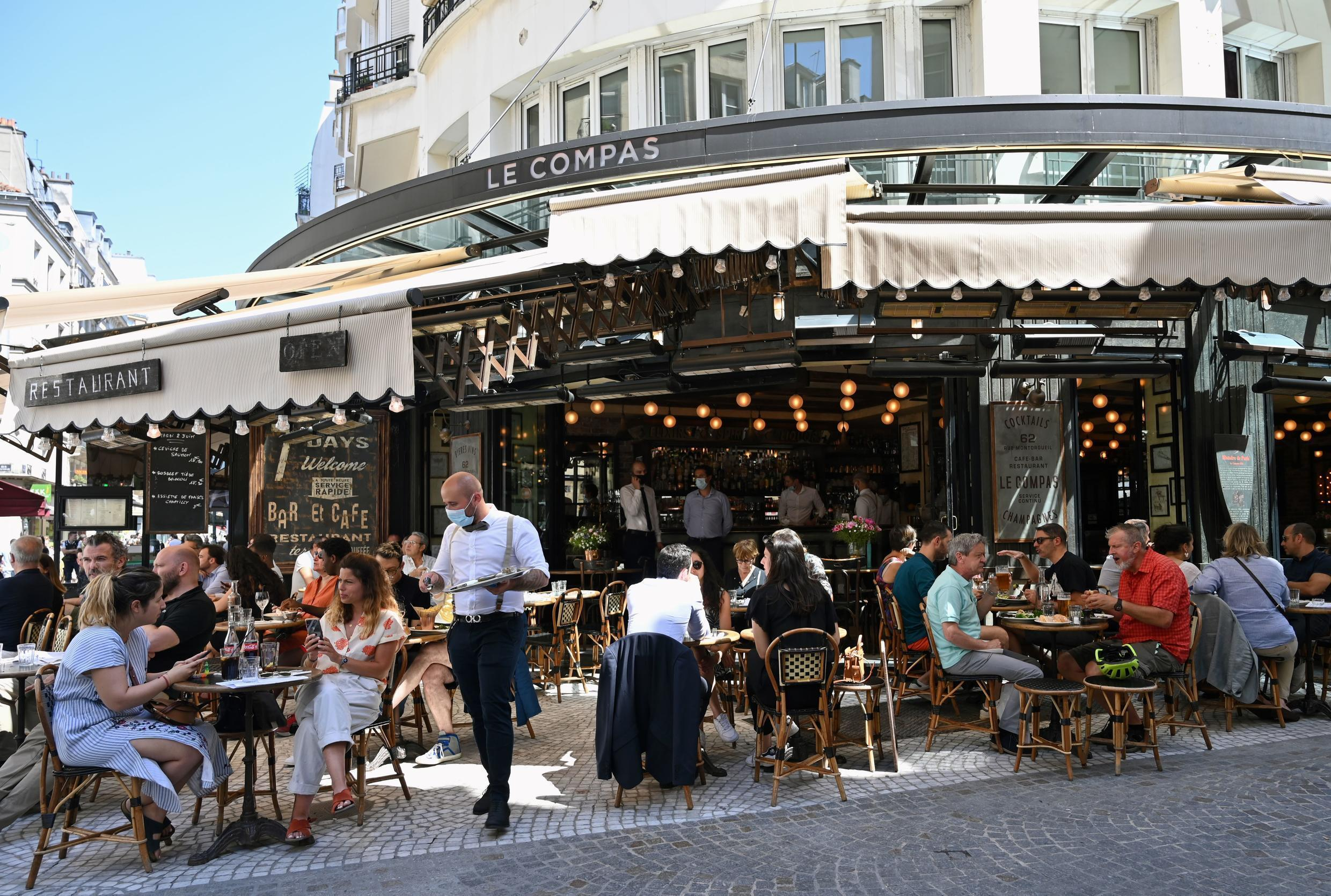 Poeple eat and drink at the terrace of the restaurant Le Compat in Paris on June 2, 2020.