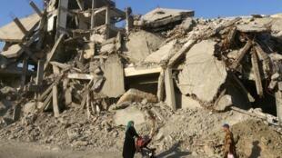 Une femme et son enfant marchent à travers les ruines de la ville de Raqqa, le 29 mai 2019 (illustration).