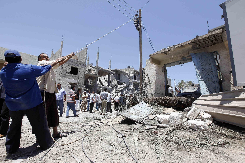 Un hombre repara un poste de tendido eléctrico en Trípoli, mientras el gobierno libio insiste en los daños causados por los bombardeos de la OTAN.