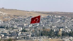 Un drapeau turc flotte devant la ville frontalière de Kobane, de l'autre côté de la frontière syrienne, l'un des objectifs militaires de l'EI (juin 2015). Si cette partie de la frontière est sécurisée, il en reste une centaine encore perméables.