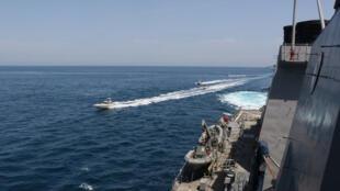 قایق های نیروی دریایی سپاه پاسداران در نزدیکی یک ناو آمریکایی در خلیج فارس.