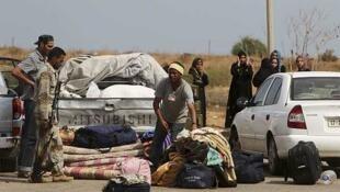 Combatientes rebeldes revisan pertenencias de familias que huyen de Sirte, el 2 de octubre de 2011.