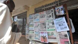 Un Camerounais parcourt la Une des journaux devant un kiosque au lendemain de l'élection présidentielle du 9 octobre 2011.
