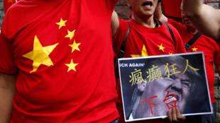 """香港的抗议者手举特朗普照片,上写""""疯狂癫人下台"""""""