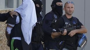 Yassin Salhi (sous le drap blanc) escorté par les policiers, le 28 juin 2015.