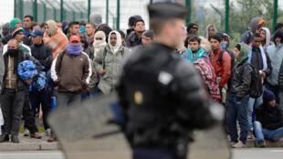 Imigrantes sem documentos esperam para serem expulsos pela polícia em Calais, na França, em 2014.