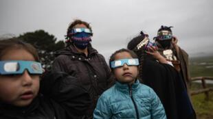 Une famille autochtone mapuche observe l'éclipse solaire totale à Carahue, La Araucania, au Chili, le lundi 14 décembre 2020.