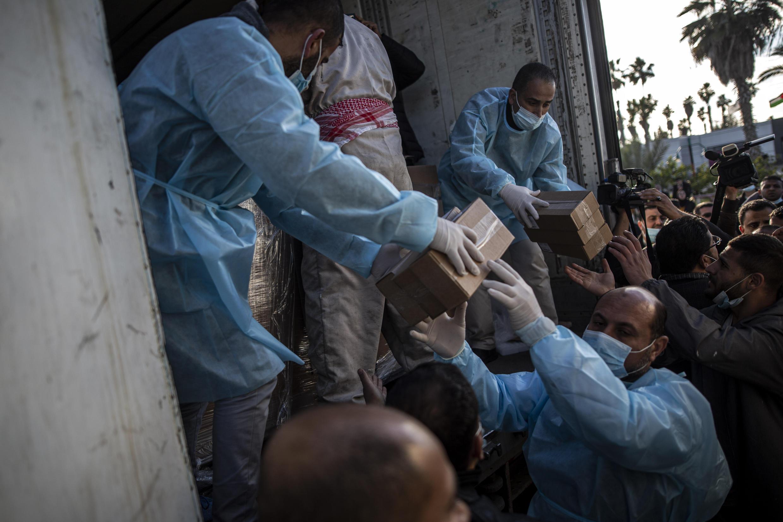 Trabajadores palestinos descargan un camión con 20.000 dosis de la vacuna rusa Sputnik V a su llegada a la Franja de Gaza, en el cruce fronterizo de Rafah con Egipto, el domingo 21 de febrero de 2021.