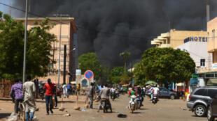 Une épaisse fumée noire s'élève dans le ciel de Ouagadougou, le 2 mars 2018, après l'explosion d'une voiture piégée près de l'état-major général des armées.