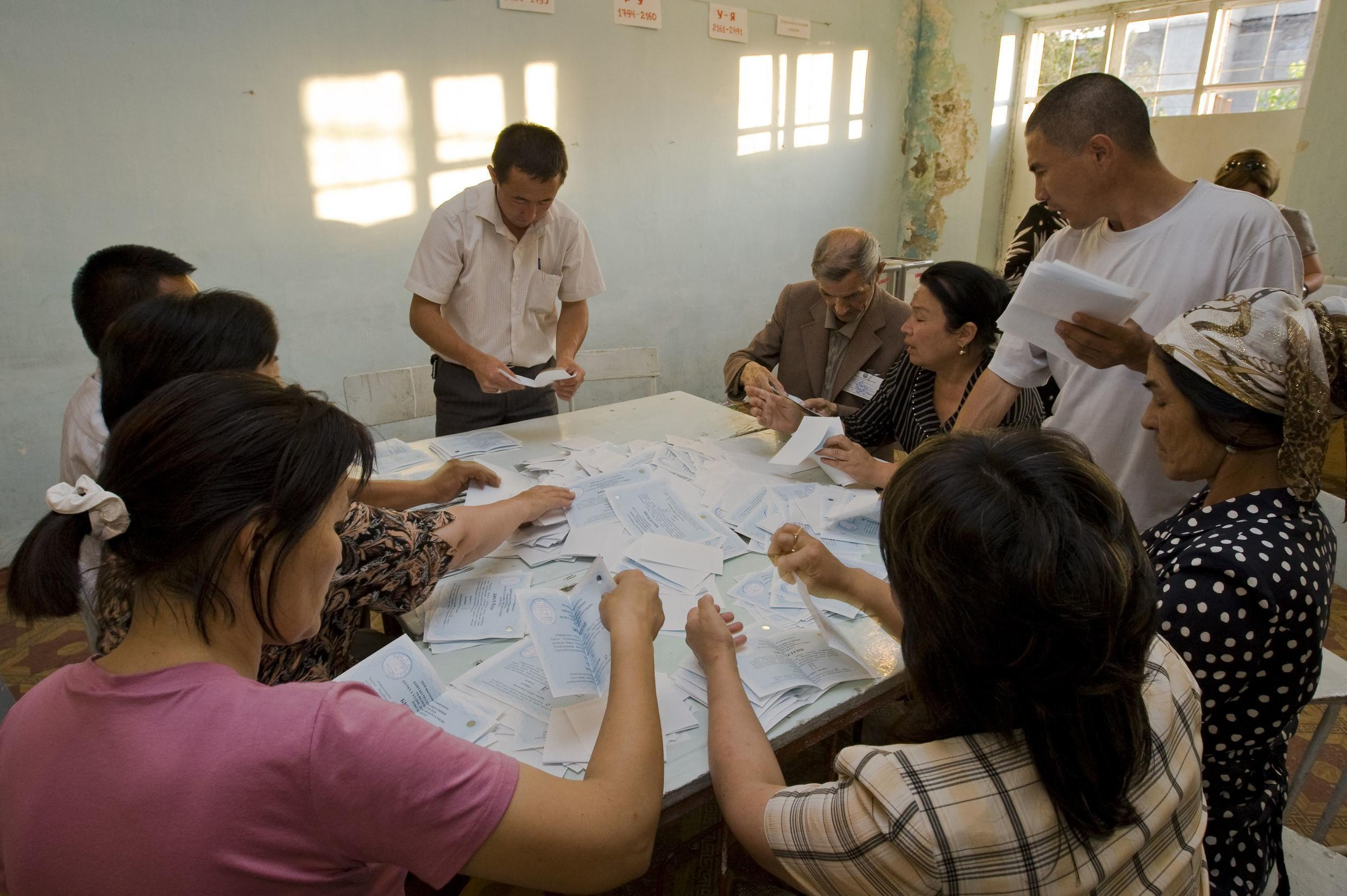 Local election committee count ballots after closing polls in Osh