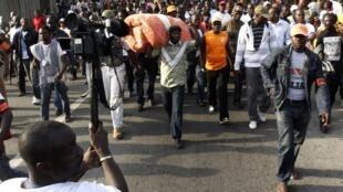 Charles Blé Goudé arrive à la manifestation samedi 26 mars 2011 en portant un matelas sur son dos, le rassemblement devant durer toute la nuit.