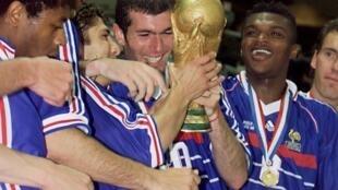 Zinédine Zidane soulève le trophée de la Coupe du monde, entouré de Bernard Diomède, Robert Pires, Bixente Lizarazu, Marcel Desailly et Laurent Blanc, après la victoire de la France, 3-0 face au Brésil, en finale de la Coupe du monde, le 12 juillet 1998 au Stade de France à Saint-Denis