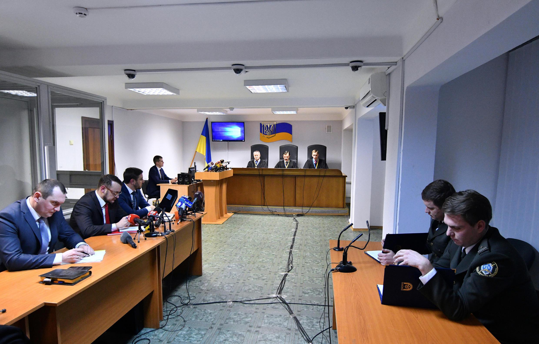 Les avocats du président ukrainien déchu, Viktor Ianoukovitch, (à gauche) et des procureurs (à droite) écoutent un panel de trois juges (C) alors qu'ils rendent le verdict, le 24 janvier 2019, à Kiev.