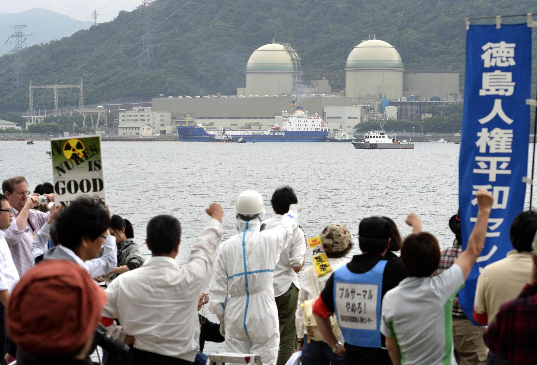 Des manifestants protestent à l'arrivée d'un cargo (C) transportant le MOX traité en France et réceptionné à la centrale nucléaire de Kansai Electric Power Co à Takahama, au Japon.