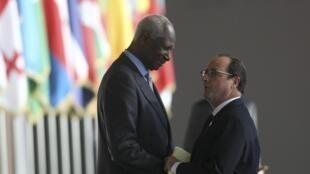 Le président français François Hollande (d.) serrant la main à Abdou Diouf avant son discours au sommet de la Francophonie, le 29 novembre 2014, à Dakar au Sénégal.