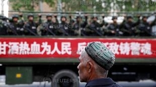A Uighur man looks on as a truck carrying paramilitary policemen travel along a street during an anti-terrorism oath-taking rally in Urumqi, Xinjiang Uighur Autonomous Region, China May 23, 2014.