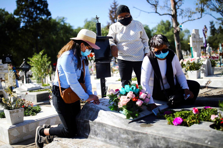 Covid-19:墨西哥染疫死亡人數在周四(2020年11月19日)越10萬大關。 Le Mexique vient de passer la barre des 100 000 personnes décédées du Covid-19, après les Etats-Unis, l'Inde et le Brésil. Dans ce cimetière de Mexico, la capitale, une famille enterre un proche décédé du coronavirus, le 16 novembre 2020.