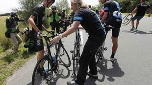 Froome gets assistance after crashing during the 163.5 km fourth stage of the Tour de France