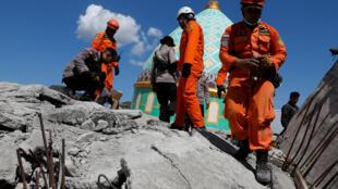 Operações de resgate a 7 de Agosto de 2018 em Pemenang, Lombok, Indonésia, junto a uma mesquita que ruíu.
