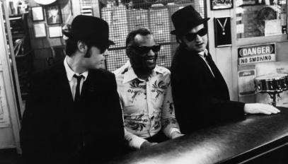 """Dan Aykroyd (gauche) et John Belushi (droite) écoutent Ray Charles jouer du piano, scène du film """"The Blues Brothers"""", 1980."""