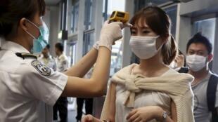 Prise de température d'une voyageuse de Busan, Corée du Sud, à son arrivée à l'aéroport de Hong Kong.