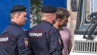 The Pussy Riot punk group member Pyotr Verzilov (R) leaves a detention centre in Moscow, only to be driven to a police station where he tweeted he and three other members were under arrest again for the night