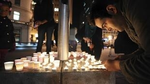 Mario Buda lights candles during the vigil for the Connecticut shooting victims