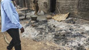 Des politiques et des habitants se tiennent près des cendres le 11 juin 2019 dans le village de Sobane, près de Sangha au Mali, après l'attaque du 9 juin.