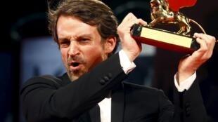 El director venezolano Lorenzo Vigas levanta el León de Oro durante la entrega de premios.