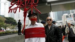 Một nghệ sĩ trên đường phố Hồng Kông trình diễn màn tự trói, để phản đối Bắc Kinh bắt cóc các nhân viên nhà sách, 10/01/2016.