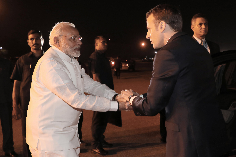 Presidente francês (à direita) Emmanuel Macron recebido pelo primeiro-ministro indiano Narendra Modi a 29 de Março de 2018 no Aeroporto militar de Nova Delhi.