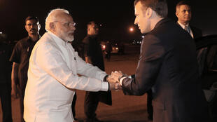 French President Emmanuel Macron (R) is welcomed by Indian Prime Minister Narendra Modi at New Delhi's military airport on Friday