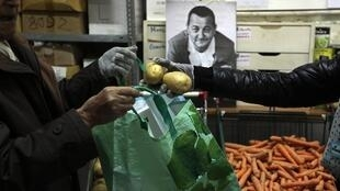 """A man holds a bag to collect food in a charity food distribution centre """"Les Restos Du Coeur""""."""