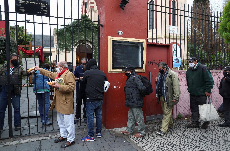 Personnes faisant la queue devant une soupe populaire organisée à l'église de Caacupe, lors de l'épidémie de coronavirus à Buenos Aires, le 23 juillet 2020.