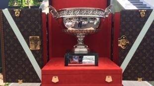 O troféu Coupe des Mousquetaires, que é entregue ao vencedor do torneio masculino de Roland Garros, ao lado das caixas Louis Vuitton, sob medida.
