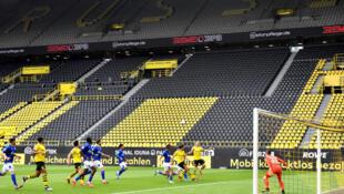 'Yan wasan Borussia Dortmund da takwarorinsu na Schalke 04, yayin fafatawa a gasar Bundesliga da ta dawo daga dohon hutun dole saboda coronavirus.16/5/2020.