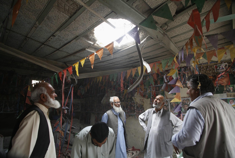 Des officiers de police inspectent un bureau de campagne du PPP après l'explosion d'une bombe à Quetta, vendredi 10 mai 2013.